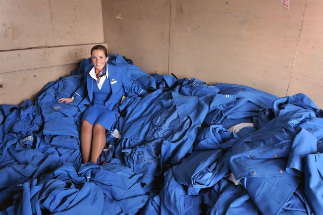 Stewardesse sitting on a stack of old uniforms re-used for the carpet
