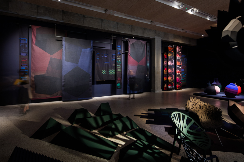 Breathing Colour – Detail of the EVENING section. Evening textiles along the wall and a shadow installation in the front.