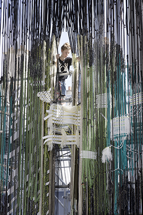 During the exhibition a team of designers weaves a weft into the warp of the Space Loom. ©Roel van Tour