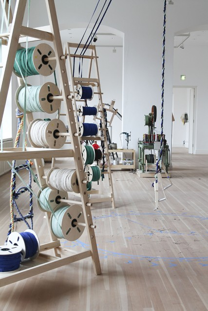 Dancing a Yarn, exhibition view of the installation with an industrial braiding machine in the background, 2021